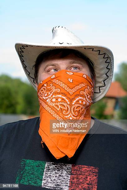 Close-up of a cowboy covering his face with a bandana