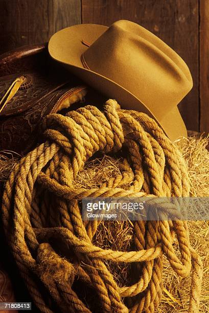 Close-up of a cowboy hat and lasso on hay