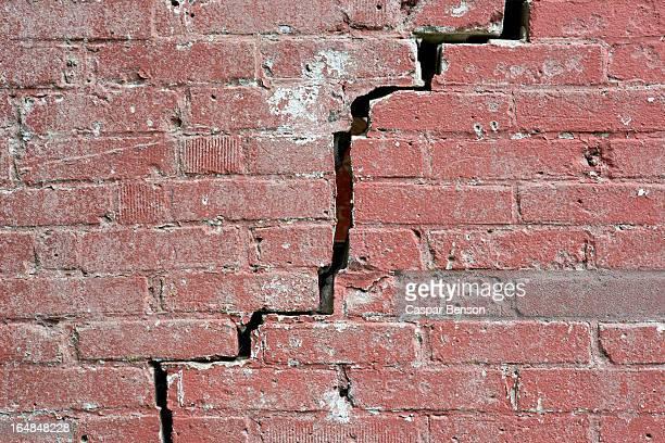 close-up of a crack running through a red brick wall - crack imagens e fotografias de stock