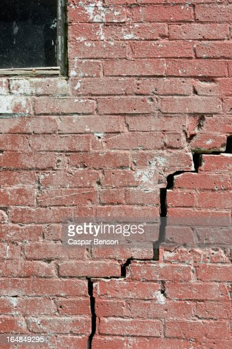 Closeup Of A Crack Running Through Red Brick Wall Stock Photo