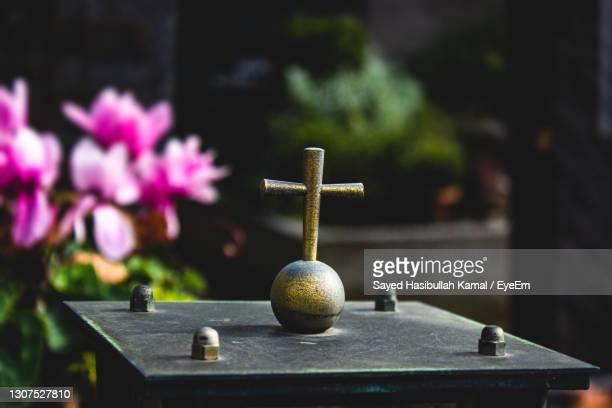 close-up of a cross symbol sculpture in a graveyard or cemetery with flowers in the background - 安らかに眠れ ストックフォトと画像