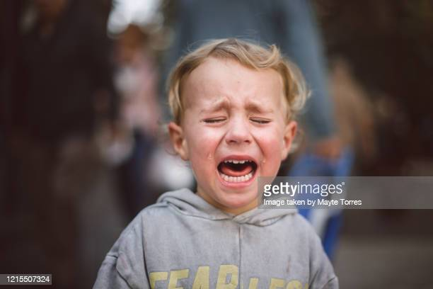 close-up of a crying boy in the street - 泣く ストックフォトと画像