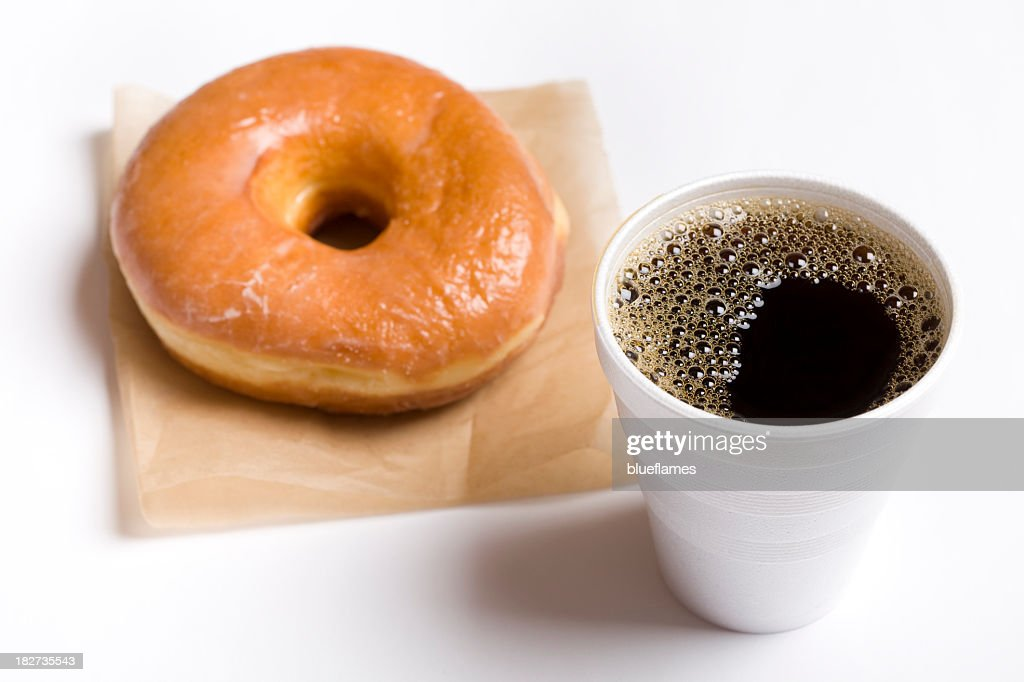 Close-up of a cup of black coffee and a glazed donut : Stock Photo