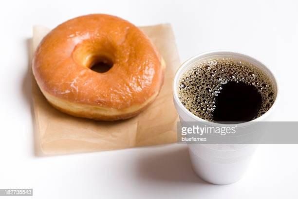 Close-up of a cup of black coffee and a glazed donut