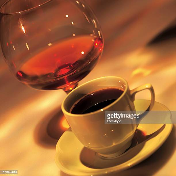 close-up of a cup of coffee with a glass of wine