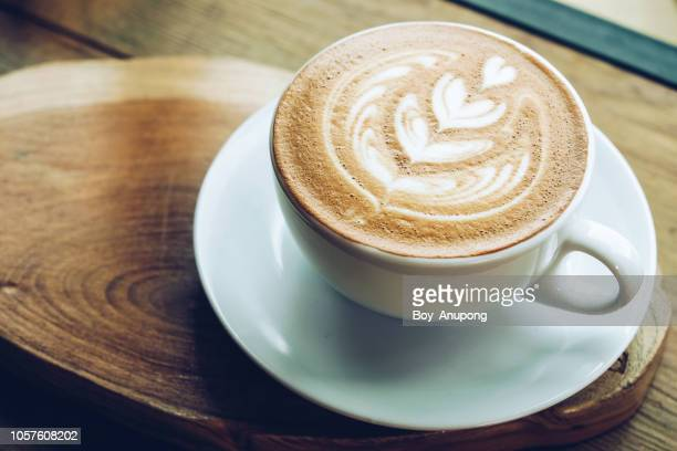 close-up of a cup of hot latte coffee on the wooden table. - art stock-fotos und bilder