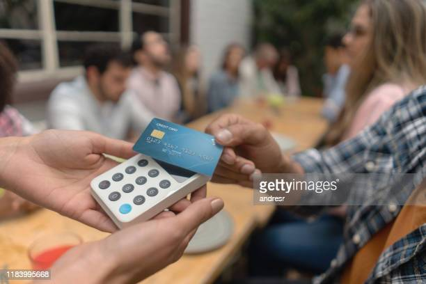 close-up of a customer at a restaurant making a contactless payment - credit card reader stock pictures, royalty-free photos & images