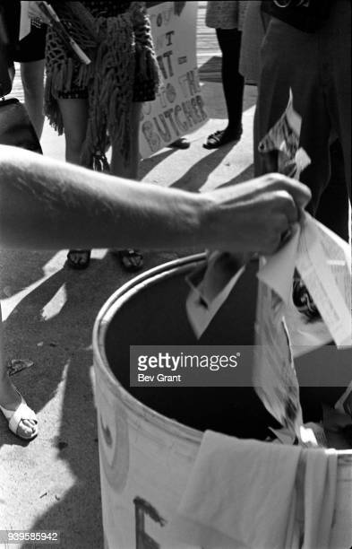 Close-up of a demonstrator's arm throwing the torn pages of a magazine into the 'Freedom Trash Can' on the Atlantic City Boardwalk during a protest...