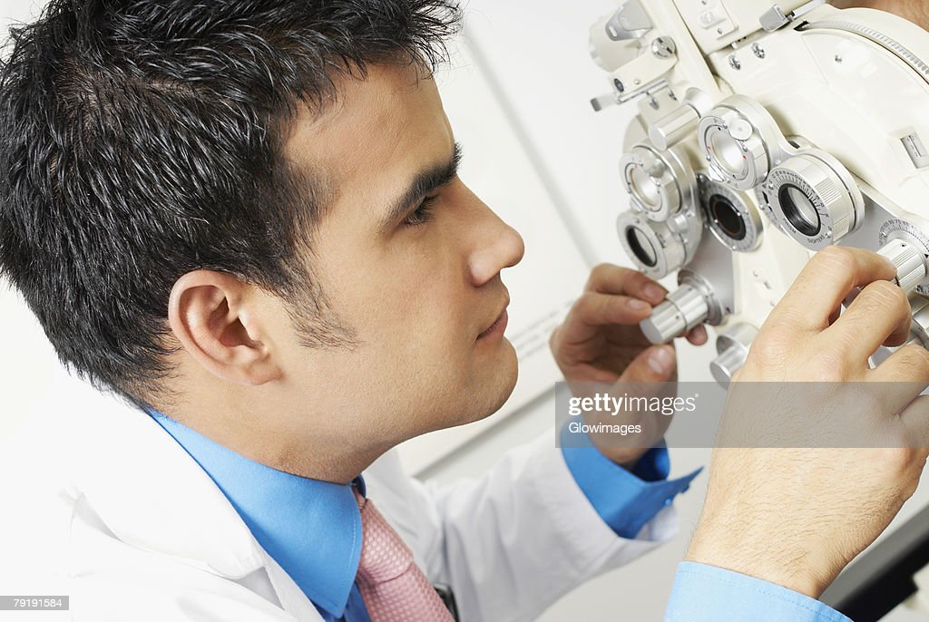 Close-up of a doctor looking through a phoropter : Foto de stock