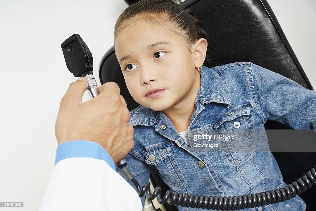 Close-up of a doctor's hand examining a girl's eye : Stock Photo