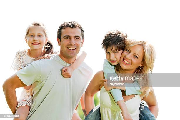 Gros plan d'une famille souriant à la caméra.