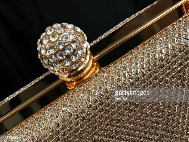 close-up of a fancy rhinestone-covered snap lock detail on a gold colored elengant purse - designelement stock-fotos und bilder