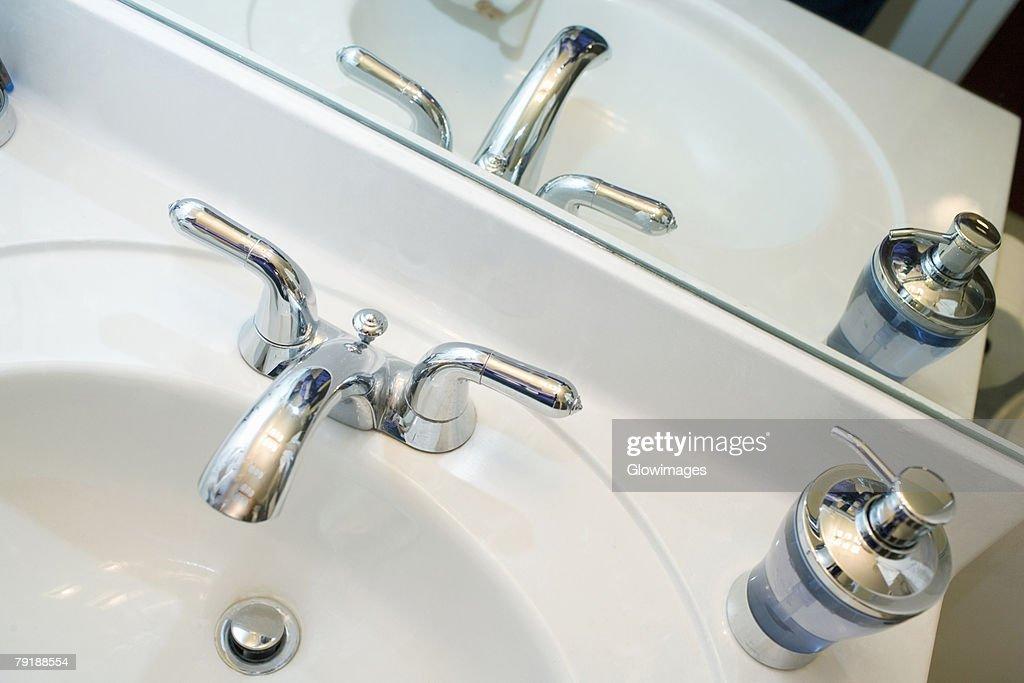 Close-up of a faucet and a soap dispenser on a bathroom sink : Foto de stock