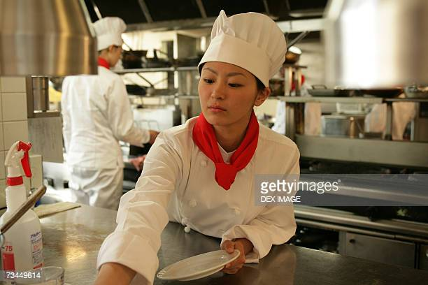 Close-up of a female chef cleaning a plate in the kitchen