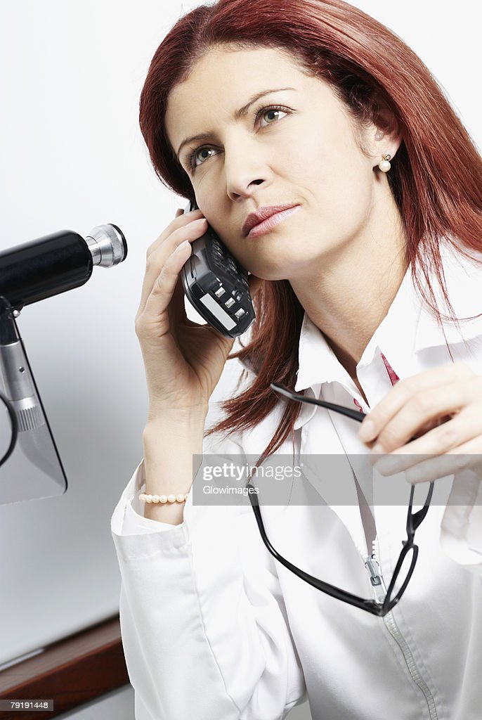 Close-up of a female doctor talking on a cordless phone : Stock Photo