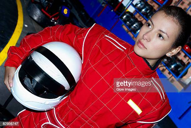 close-up of a female go-cart racer holding a crash helmet under her arm - レーシングドライバー ストックフォトと画像