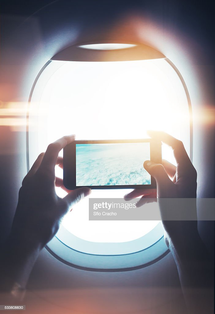 Close-up of a female hand holding smartphone and taking photos through porthole : Foto stock