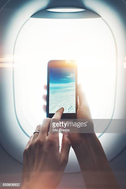 Close-up of a female hand holding smartphone and taking photos through porthole