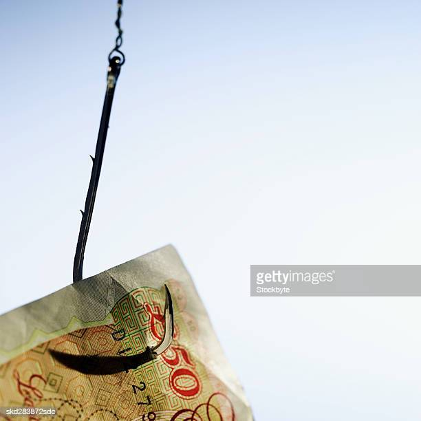 close-up of a fifty pound note hanging on fishhook - fifty pound note stock photos and pictures