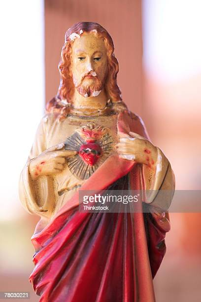 close-up of a figurine of jesus christ opening his robe and pointing to his heart. - thinkstock stock photos and pictures