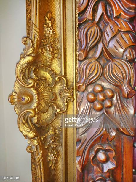 Closeup of a fine art, ornate, gilded, carved, classic style picture frame and carved detail of a throne chair.