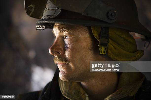 close-up of a firefighter looking sideways - capacete de bombeiro - fotografias e filmes do acervo