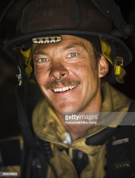 close-up of a firefighter smiling - fire protection suit stock photos and pictures