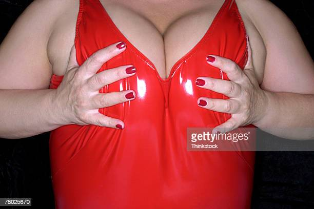close-up of a full figured woman holding her breasts in a red vinyl swimsuit. - voluptuous breasts stock pictures, royalty-free photos & images