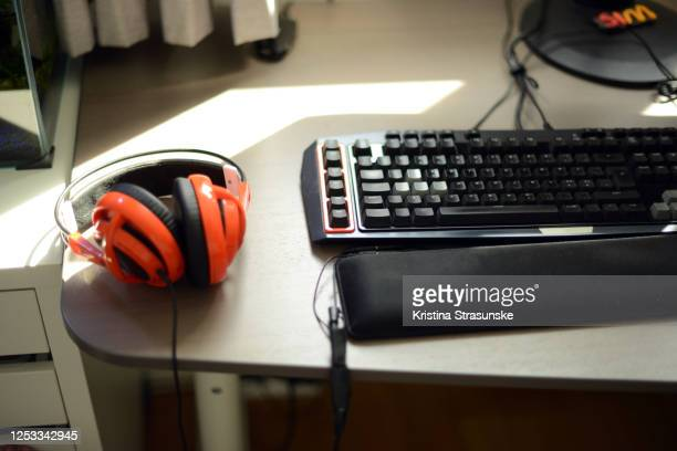 close-up of a gaming keyboard and orange colored headphones on a desk - kristina strasunske stock pictures, royalty-free photos & images