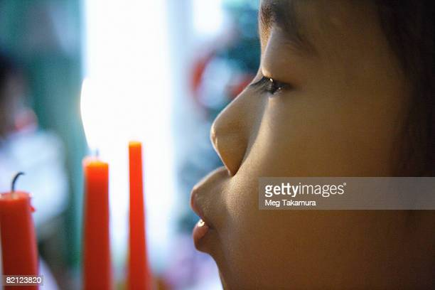 Close-up of a girl blowing out a candle