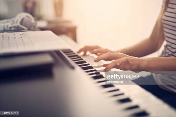 Closeup of a girl composing on digital piano