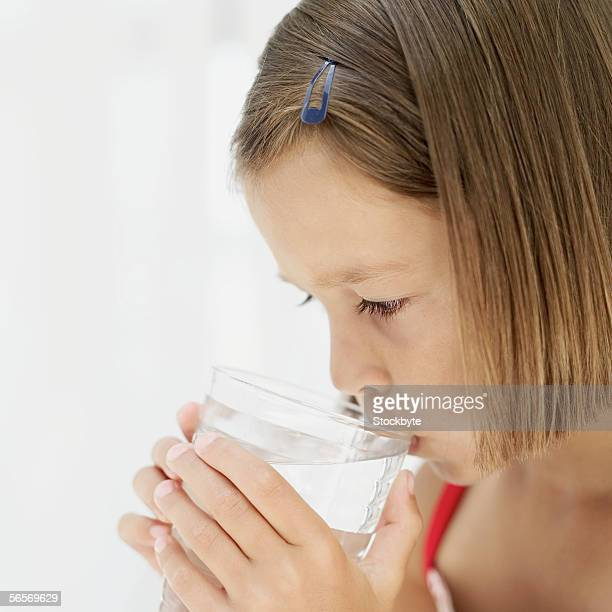 close-up of a girl drinking water from a glass