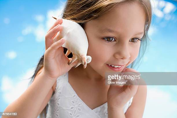 Close-up of a girl holding a seashell close to her ear