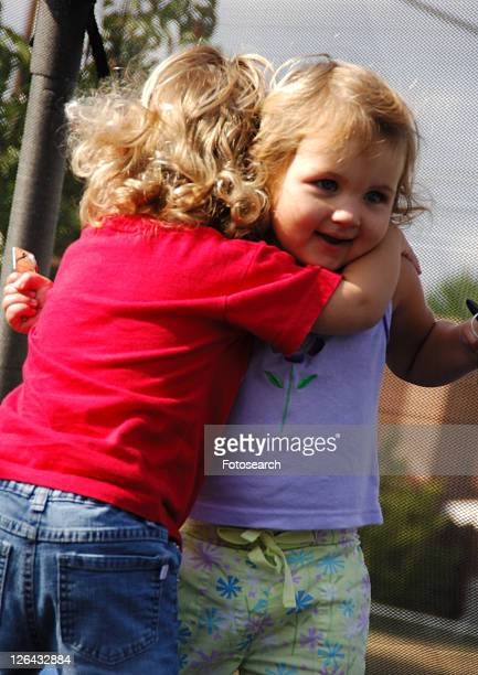 close-up of a girl hugging another girl - little girls bare bum stock pictures, royalty-free photos & images