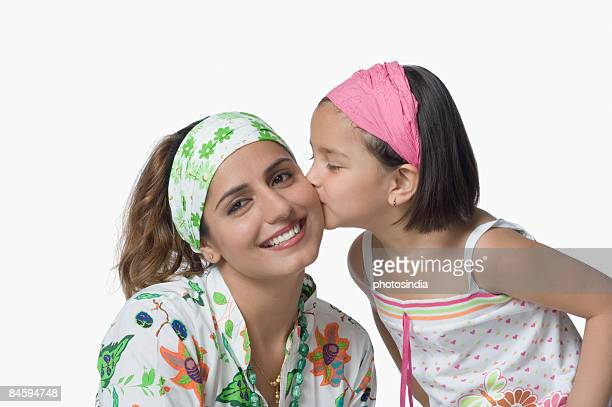 close-up of a girl kissing her mother and smiling - indian girl kissing stock photos and pictures