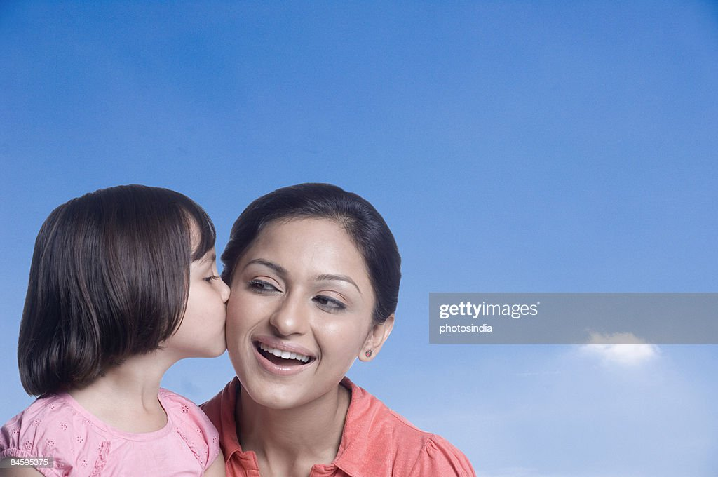 Close-up of a girl kissing her mother : Stock Photo