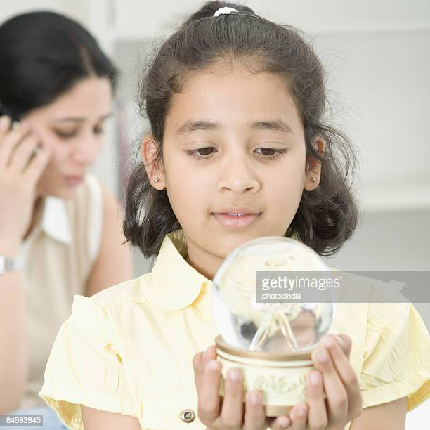 Close-up of a girl looking at a snow globe and her mother talking on a mobile phone behind her