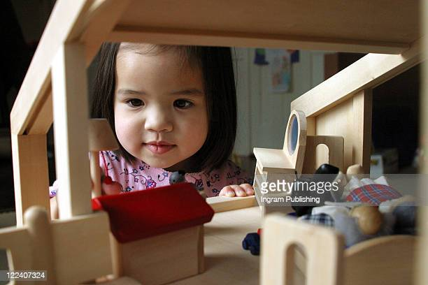 Close-up of a girl playing with a dollhouse
