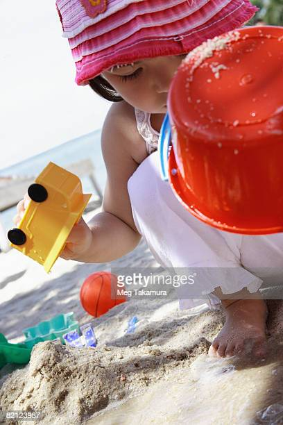 Close-up of a girl playing with toys on the beach