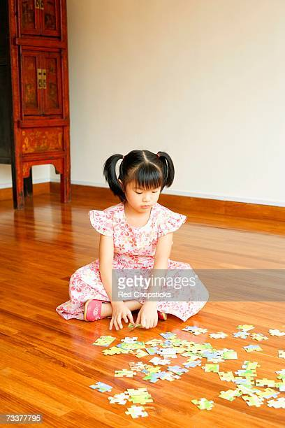Close-up of a girl sitting on the floor and playing with a jigsaw puzzle
