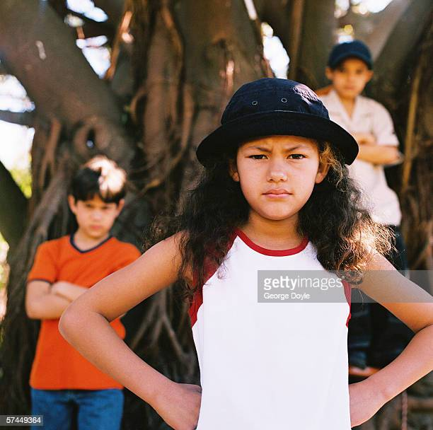 close-up of a girl (8-10) standing ahead of two boys and frowning