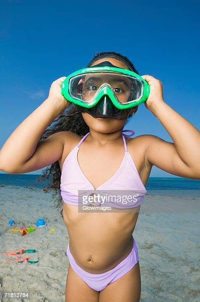 Close-up of a girl standing on the beach and wearing a scuba mask