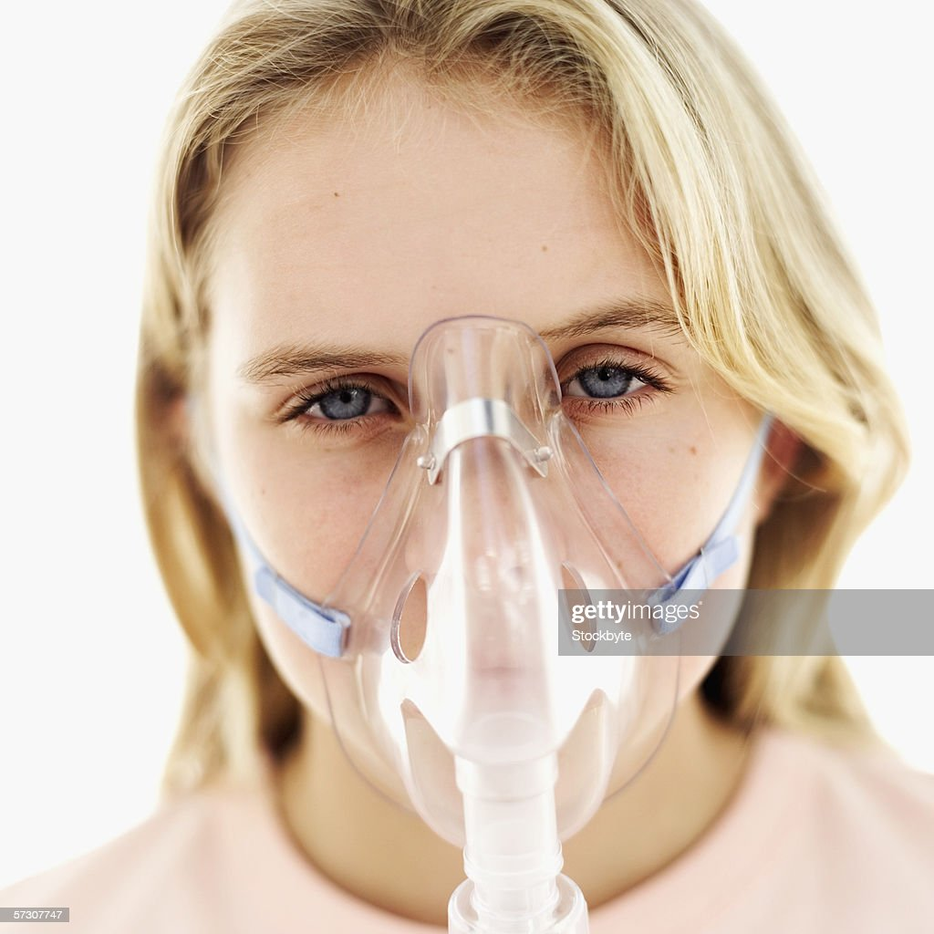 Close-up of a girl (11-13) wearing an oxygen mask : Stock Photo