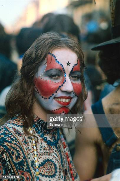 Closeup of a girl with her face painted smiles for the camera Her face paint is creatively designed which is a Mardi Gras tradition