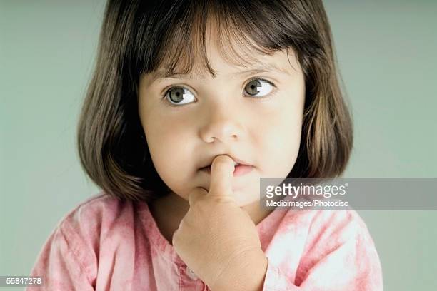 Close-up of a girl with her finger in her mouth