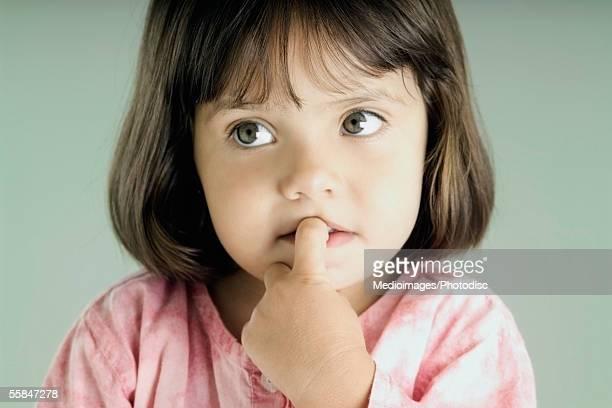 close-up of a girl with her finger in her mouth - chupando dedo - fotografias e filmes do acervo