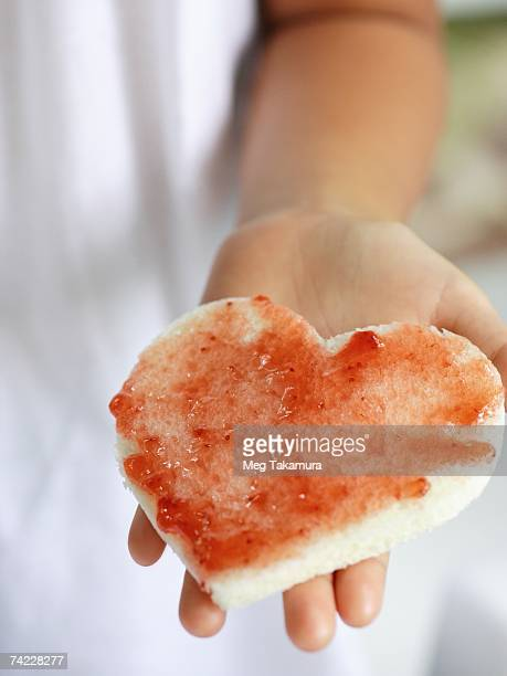 Close-up of a girl's hand holding a heart shaped bread