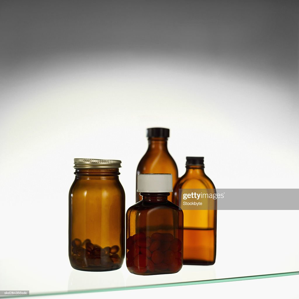 Close-up of a glass cabinet containing cough syrup and container of tablets : Stock Photo