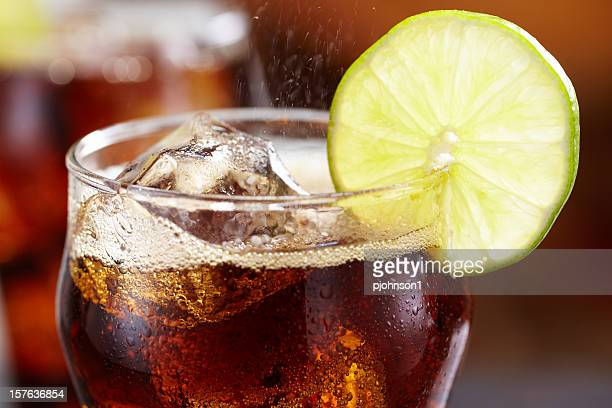 Close-up of a glass of cola with ice and lemon garnish