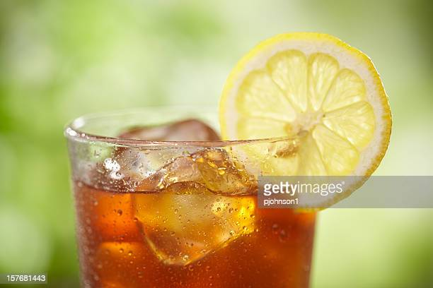 A close-up of a glass of iced tea with lemon